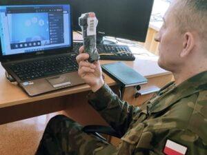 Instruktor prezentujacy szkolonym uczniom środki medyczne wchodzące w skład indywidualnego wyposażenia żołnierza
